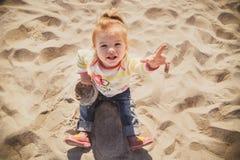 坐和使用在沙子在海滩,上面的小婴孩、小女孩蓝色牛仔裤的,桃红色鞋子和五颜六色的套头衫画象  库存图片