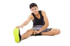 坐和做舒展的年轻健身人锻炼 图库摄影