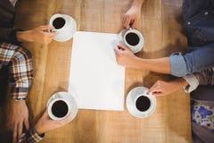 坐和喝咖啡的朋友 免版税图库摄影