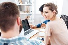 坐和工作与两个商人的愉快的妇女在办公室 免版税库存照片