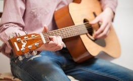 坐和弹吉他的牛仔裤的人 免版税图库摄影
