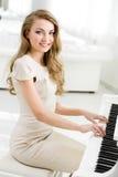 坐和弹钢琴的钢琴演奏家画象 免版税图库摄影