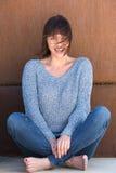 坐和微笑与风吹的头发的妇女 库存照片