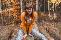 坐和微笑在秋天公园的愉快的妇女 库存图片