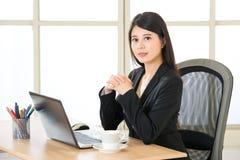 坐和微笑对书桌的年轻亚洲女实业家 库存图片