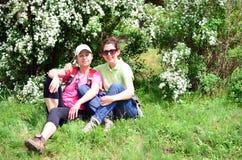 坐和拥抱在开花的白色灌木下的游人妇女 3个照相机长沙发系列女孩查找关于坐的母亲橙色纵向他们那里 免版税库存照片