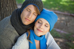 坐和拥抱在有眼睛的公园的逗人喜爱的夫妇关闭了 免版税图库摄影