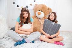 坐和拥抱枕头的两个哀伤的疲乏的姐妹 免版税库存照片