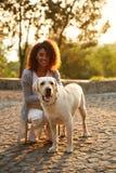 坐和拥抱狗的便衣的年轻微笑的夫人在公园 库存图片