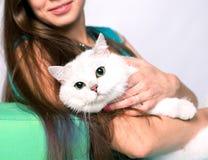 坐和拥抱猫的一个微笑的女孩的画象 库存图片