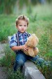 坐和拥抱他的玩具熊,有悬挂装置格子花呢上衣的时髦的牛仔裤的小逗人喜爱的男孩 childhoo记忆  库存图片