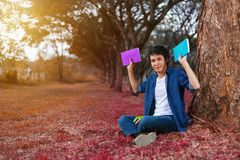 坐和拿着一本书的年轻人在公园 免版税库存照片