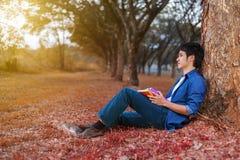 坐和拿着一本书的年轻人在公园 免版税图库摄影