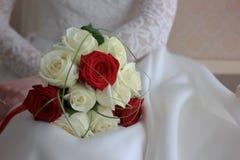 坐和拿着婚礼花束的白色婚礼礼服的新娘 库存图片