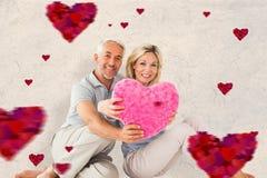 坐和拿着心脏枕头的愉快的夫妇的综合图象 免版税库存图片