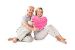 坐和拿着心脏枕头的愉快的夫妇 免版税库存图片