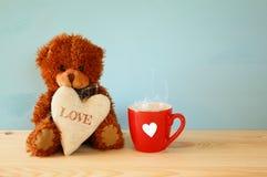 坐和拿着心脏的玩具熊在咖啡旁边 免版税库存照片