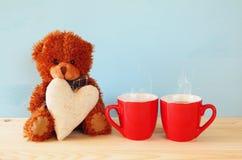 坐和拿着心脏的逗人喜爱的玩具熊 免版税库存照片