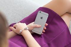 坐和拿着新的iPhone 6空间的妇女灰色 库存图片