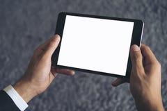 坐和拿着有空白的白色屏幕的商人的大模型图象黑片剂个人计算机有灰色地毯的 库存照片