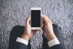 坐和拿着有空白的黑屏幕的商人的大模型图象白色手机有灰色地毯的 库存图片