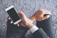 坐和拿着有空白的黑屏幕的商人的大模型图象白色手机有灰色地毯的 免版税库存照片