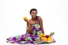 坐和拿着桔子的逗人喜爱的沉思非裔美国人的妇女 免版税库存照片