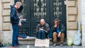坐和拿着烧瓶的无家可归的人 免版税库存照片
