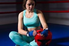 坐和拿着盔甲的运动女性拳击手 库存图片