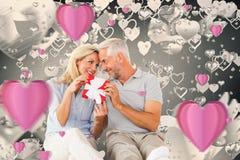 坐和拿着礼物的愉快的夫妇的综合图象 库存照片