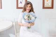 坐和拿着花的花束在咖啡馆的微笑的妇女 免版税库存图片
