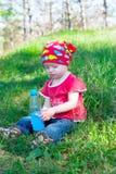 坐和拿着水瓶的小美丽的女孩手中 库存图片