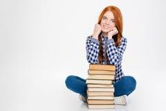坐和摆在与书的美丽的愉快的年轻红头发人女孩 免版税库存照片