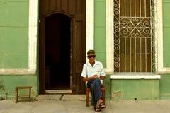 坐和摆在摆在与雪茄的老人在城市三 图库摄影