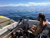 坐和放松在他的小船船尾的人,他钓鱼为 库存图片