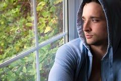 坐和注视在窗口外面的英俊的年轻人 免版税库存照片