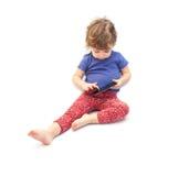 坐和演奏智能手机的小孩 免版税库存照片
