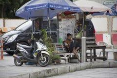 坐和演奏智能手机的摩托车出租汽车泰国人人民 免版税库存照片