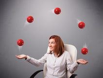 坐和玩杂耍与红色球的女孩 免版税库存照片