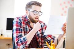 坐和看图纸的严肃的人在办公室 免版税图库摄影