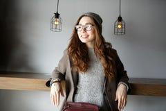 坐和看在咖啡馆的快乐的可爱的少妇 库存照片