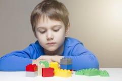 坐和看对五颜六色的塑料建筑玩具块的哀伤的孩子桌 库存图片