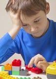 坐和看对五颜六色的塑料建筑玩具块的被集中的孩子桌 免版税图库摄影
