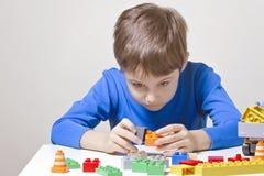 坐和看对五颜六色的塑料建筑玩具块的被集中的孩子桌 库存照片