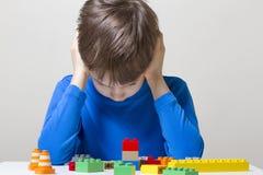 坐和看对五颜六色的塑料建筑玩具块的被集中的孩子桌 免版税库存图片