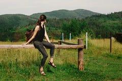 坐和看山,夏天t的时髦的行家妇女 库存照片