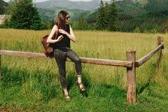 坐和看山,夏天t的时髦的行家妇女 免版税库存照片
