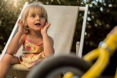 坐和看平衡自行车的年轻白肤金发的儿童女孩 温暖的日落光 家庭夏天海上o的旅行假期 免版税库存照片