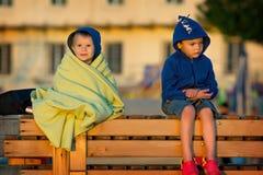 坐和看日出的两个男孩 库存图片
