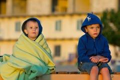 坐和看日出的两个男孩 免版税库存图片